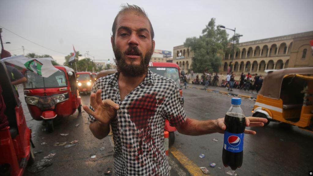العراقيون يتسلحون بالمشروبات الغازية لمواجهة المسيل للدموع وما دور الاقنعة الزرقاء؟