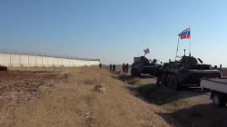 Asayish forces dig a trench in front of a Turkish military crossing