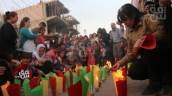 People in al-Qamishli light candles in honor of the 2016 bombing victims