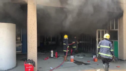 Civil Defense teams extinguish a fire in a library in Baghdad