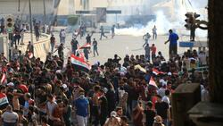 Security forces try to disperse a protest in Tahrir square in Baghdad with live bullets
